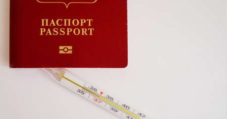 foreign passport and thermometer on white background