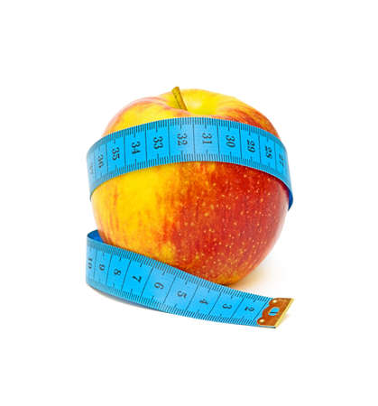 red apple and measuring tape close up on white background