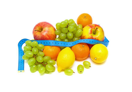 Still Life. fresh fruits and a measuring tape on white background.