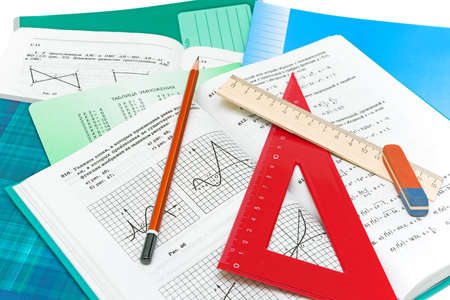 mathematics textbook, notebook, pencil and ruler closeup on white background