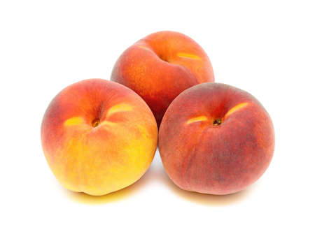 three ripe peach close up on white background