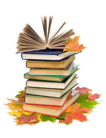 stacked: open book on a pile of books and autumn maple leaves closeup on white background