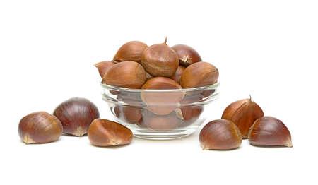 Chestnuts (Castanea sativa) in a glass bowl closeup on white background