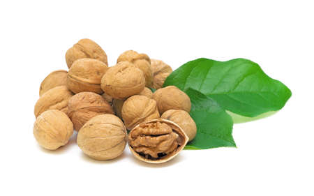 handful of walnuts and green leaves on white background close-up