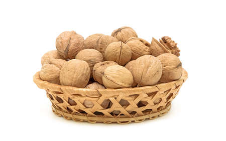 walnuts in a wicker basket on a white background closeup photo
