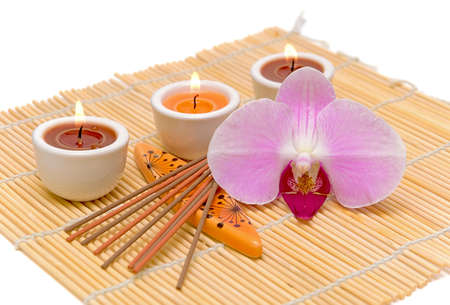 spa concept (candles, incense sticks and orchid) on a white background closeup photo