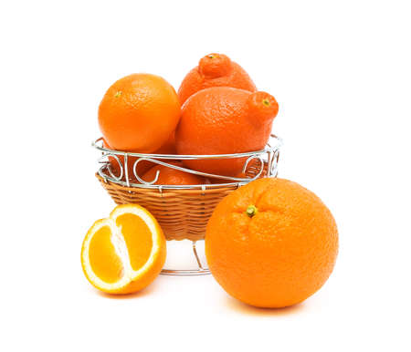 Ripe and juicy oranges and tangerines captured a vase on a white background closeup photo