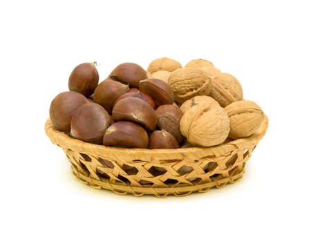 sweet chestnuts and walnuts are in a wicker basket on a white background closeup Stock Photo - 11762885