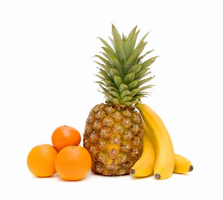 Fresh fruit: oranges, pineapples and bananas on white background close-up.
