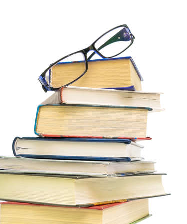 a large stack of books and glasses closeup on white background