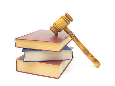 a stack of three books and gavel on white background close-up photo
