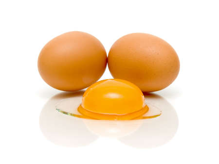 two eggs and egg yolk closeup on white background photo
