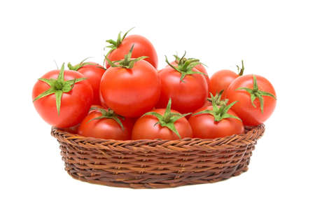 ripe tomatoes in a wicker basket isolated on white background photo