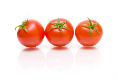 three ripe cherry tomato with reflection on white background close-up photo