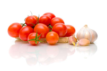 ripe tomatoes and garlic on a white background with reflection closeup