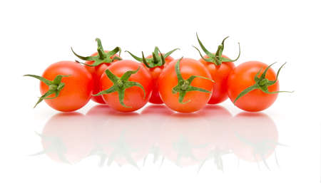 seven ripe tomatoes on a white background with a reflection of a close-up