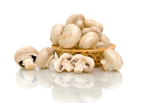 mushrooms (Agaricus) in basket on white background with a reflection of a close-up