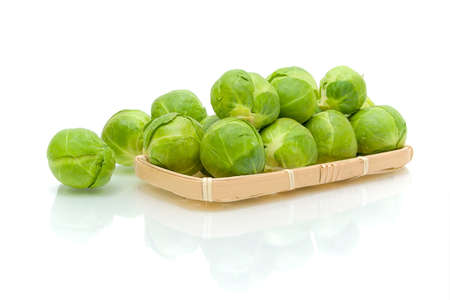 Brussels sprouts in a basket on a white background with reflection