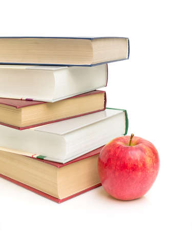 red apple and a stack of books on a white background close-up
