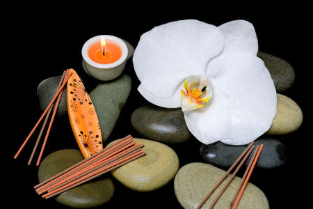alternative rock: spa composition on a black background. orchid, sea stones, candle and incense sticks.