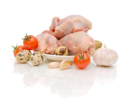 quaglia: Carcasse di quaglia freschi, uova di quaglia e verdure su sfondo bianco close-up della riflessione
