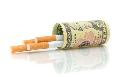 Los cigarrillos y el close-up dinero en un fondo blanco. El concepto - h�bitos caros. photo
