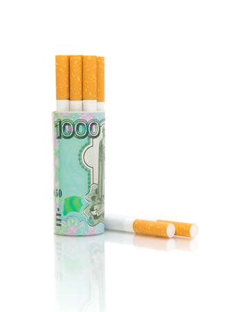 Cigarettes and banknotes on a white background. The concept - expensive habits. photo