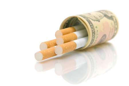 Cigarettes in U.S. dollars isolated on a white background with reflection closeup photo