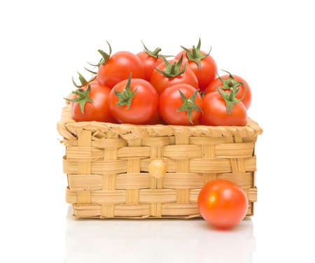 ripe tomatoes in a wicker basket isolated on white close-up of the reflection photo
