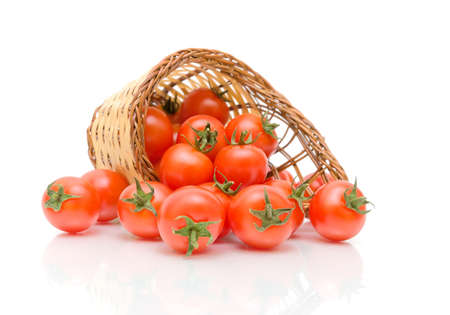 red cherry tomatoes in a woven basket on a white background