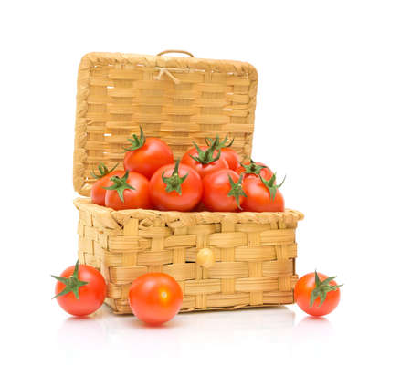 wicker basket full of ripe tomato isolated on white background photo