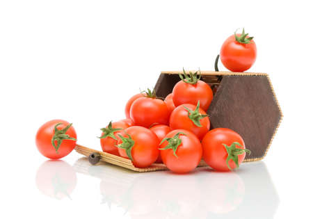 ripe cherry tomatoes in a bamboo box on a white background with reflection photo
