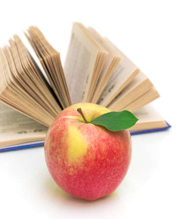 ripe apple on the background of an open book closeup on white background photo