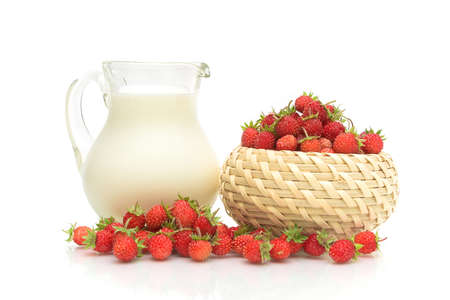 pitcher of milk and ripe wild strawberries isolated on white background