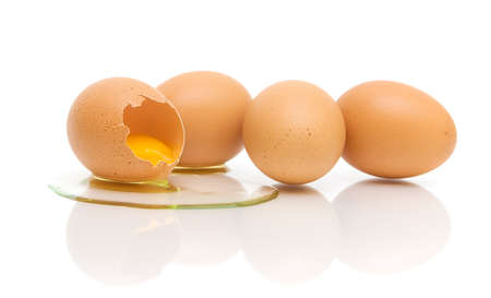 one broken and three whole eggs on a white background with reflection closeup photo