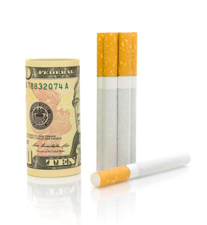 Expensive habits. U.S. $ 10 and cigarettes on a white background with reflection. photo