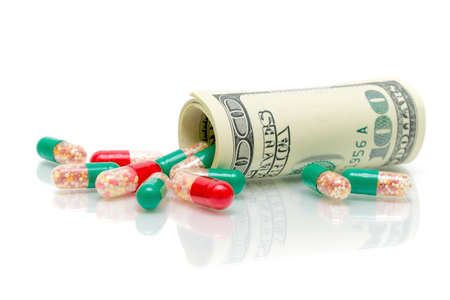 money and medical drugs on a white background with reflection closeup photo