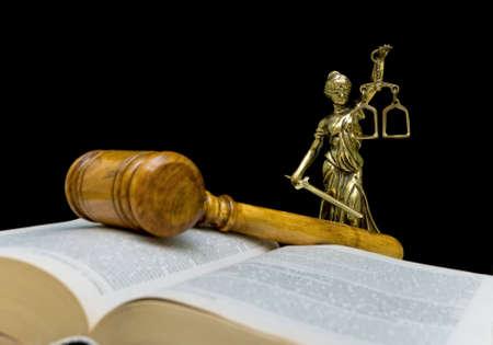 orden judicial: Estatua de la justicia sobre un fondo negro. Mazo y libro de ley en el primer plano fuera de foco. Foto de archivo