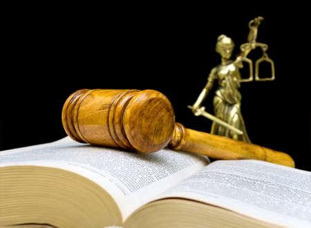 giustizia: martelletto, libro di diritto e la statua della giustizia su sfondo nero
