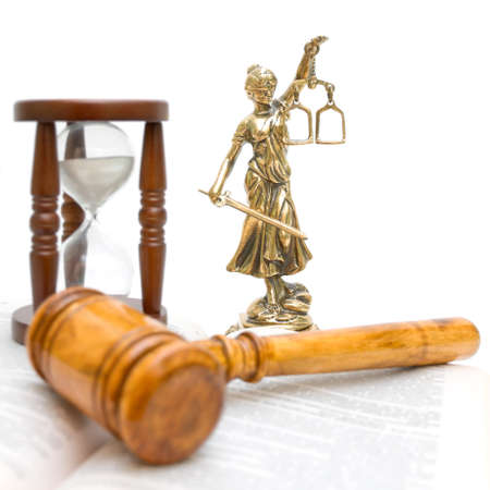 statue of justice, gavel, law book and hourglass on a white background close-up