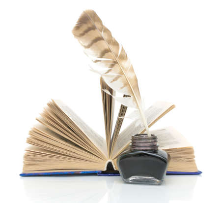 pen, inkwell and an open book on a white background with reflection closeup photo