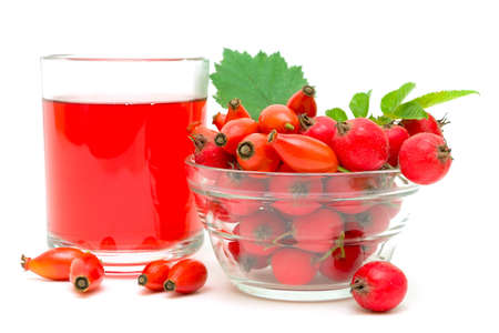 ripe rose hips, hawthorn in a glass bowl and a drink isolated on white background