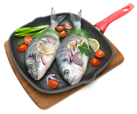 daurade: dorado fish and vegetables in a pan isolated on white background