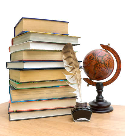 stack of various books, pen in the ink and vintage globe on white background photo