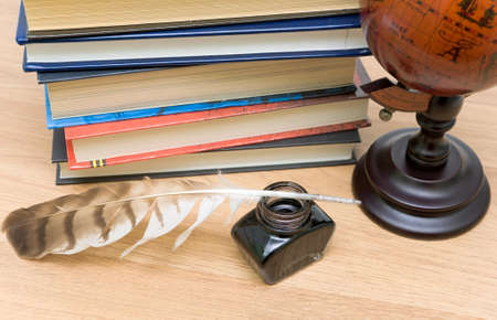school supplies close-up. inkstand, pen, various books and globe. horizontal photo. photo