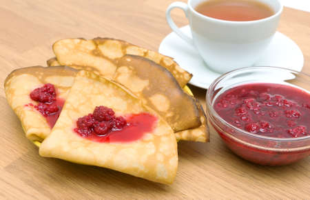 Pancakes with raspberry jam and a cup of tea on a wooden board photo