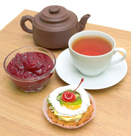 cake with fruit, cranberry jam, a cup of tea and a clay pot on a wooden board photo