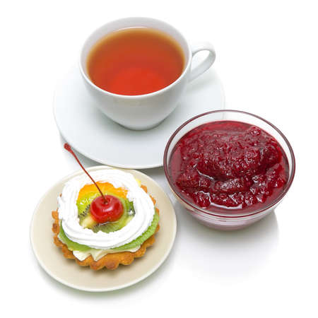 cake with fruit, cranberry jam and a cup of tea on a white background. Top view. photo