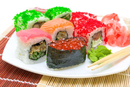 Japanese cuisine. Various sushi rolls with ginger and wasabi close-up. photo