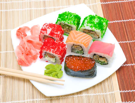 Japanese cuisine. Various sushi rolls with ginger and wasabi - top view. photo